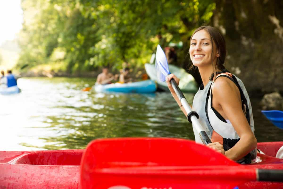 Girl in sit-on-top kayak wearing a life jacket and holding a paddle