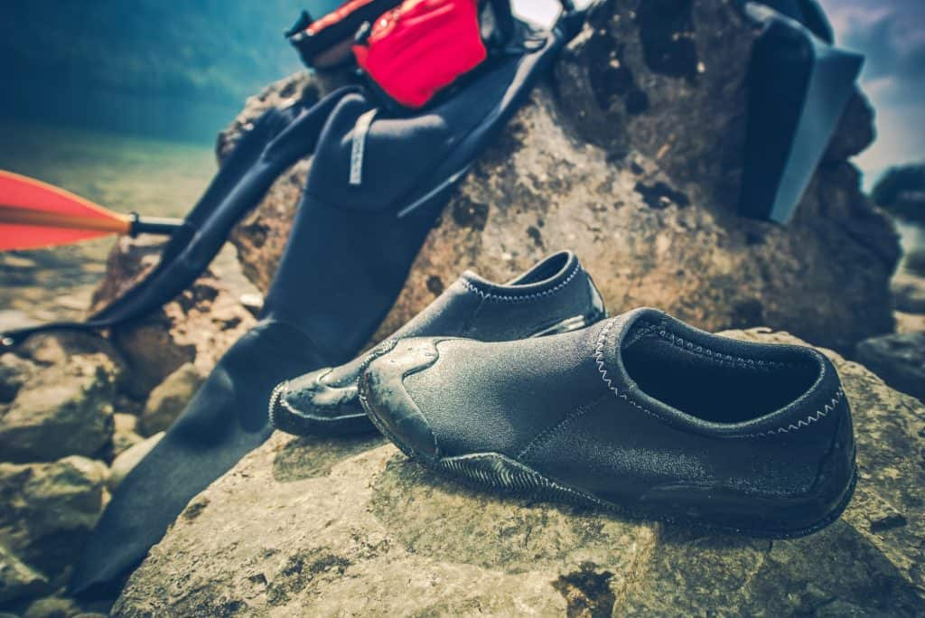 Whats to wear kayaking - wetsuit and kayaking shoes drying on a rock