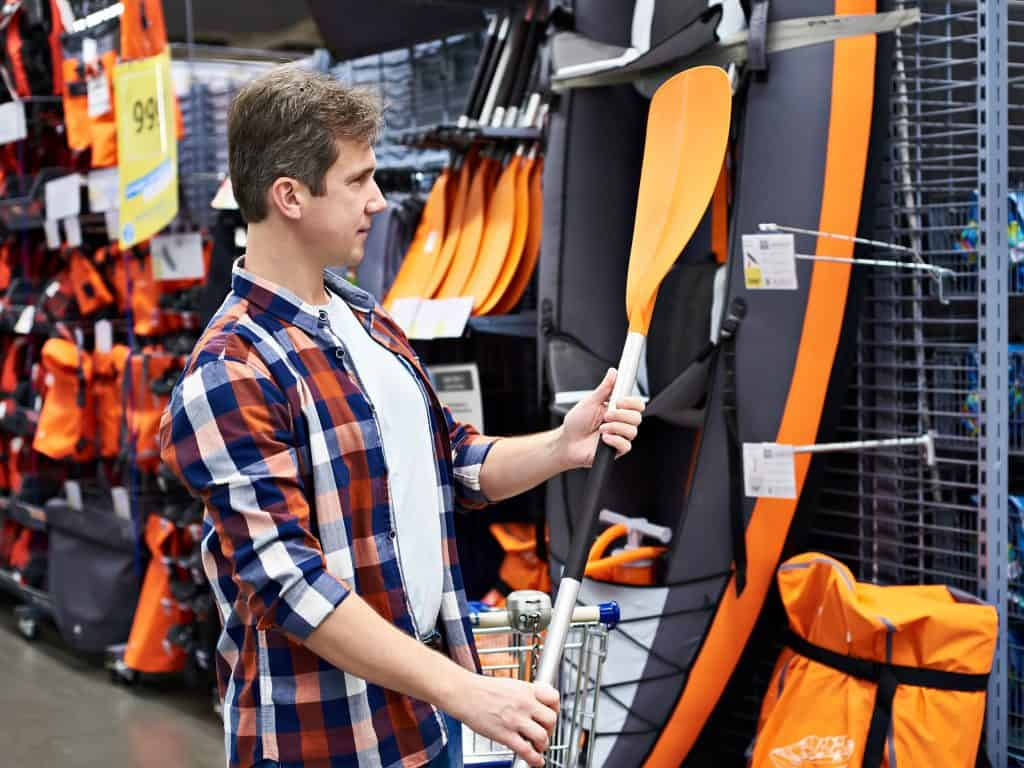 Man with a paddle for a sports boat kayak in a store