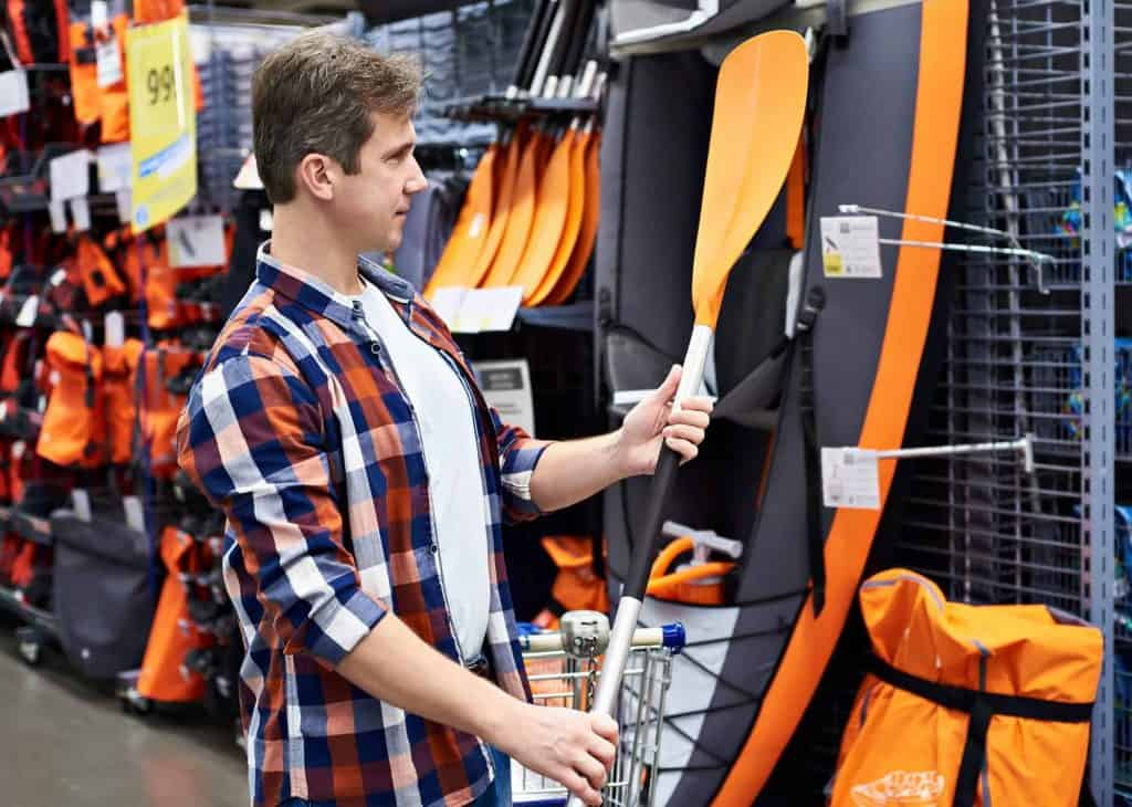 Man with paddle for sport boat kayak in store