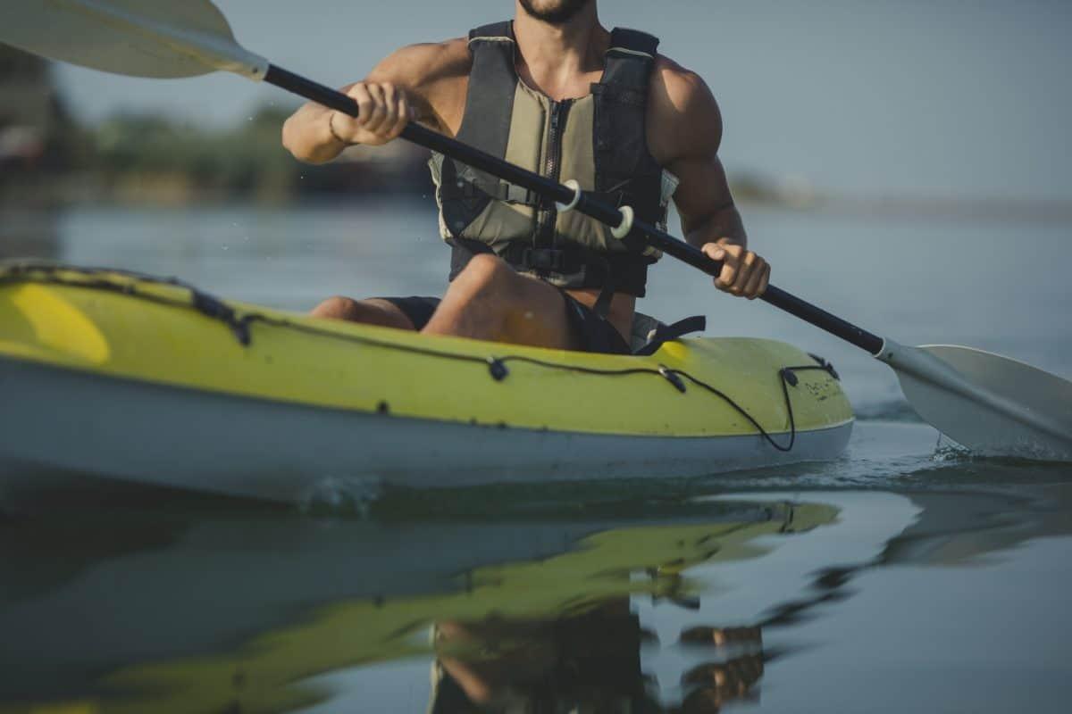 Caucasian man kayaker paddling on the river in life jacket