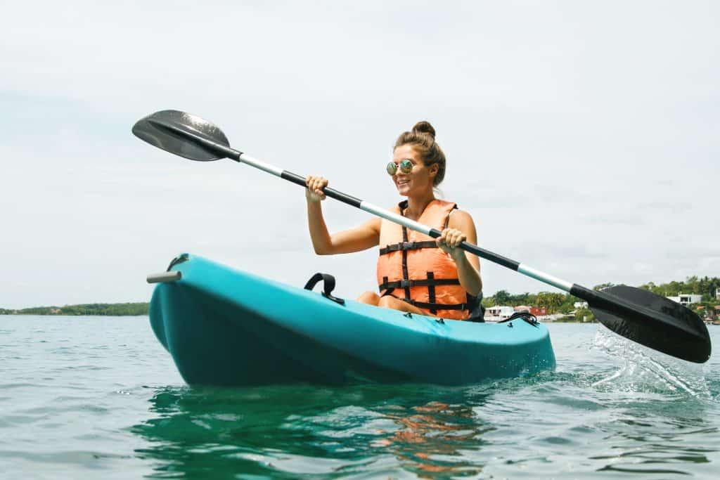 Girl paddles in orange kayak life vest