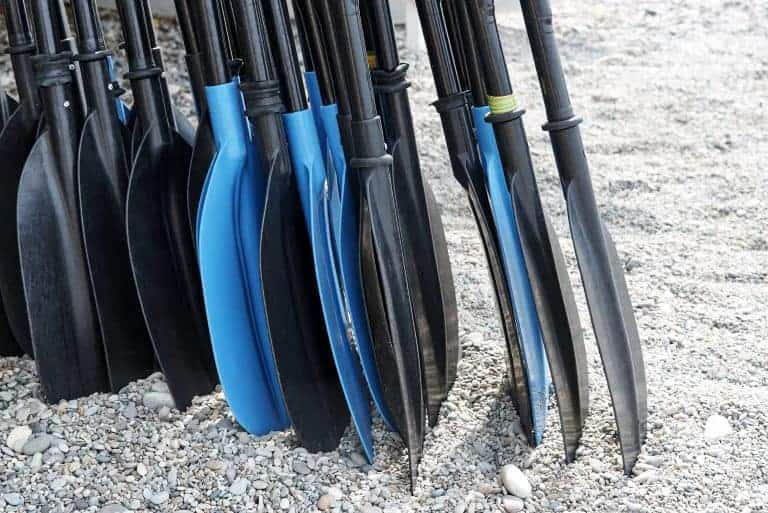 A pile of kayak paddle on the beach close up.