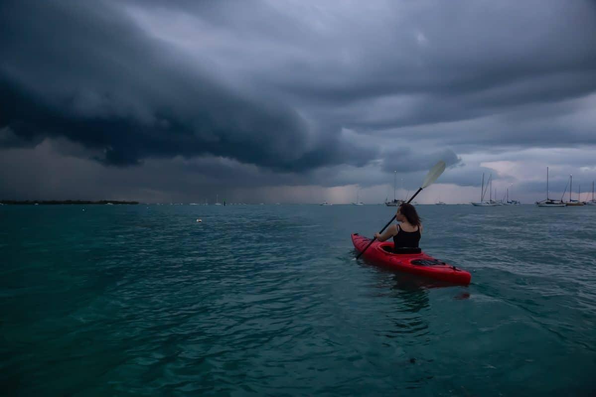 Adventurous girl on a red kayak is kayaking towards a thunderstorm