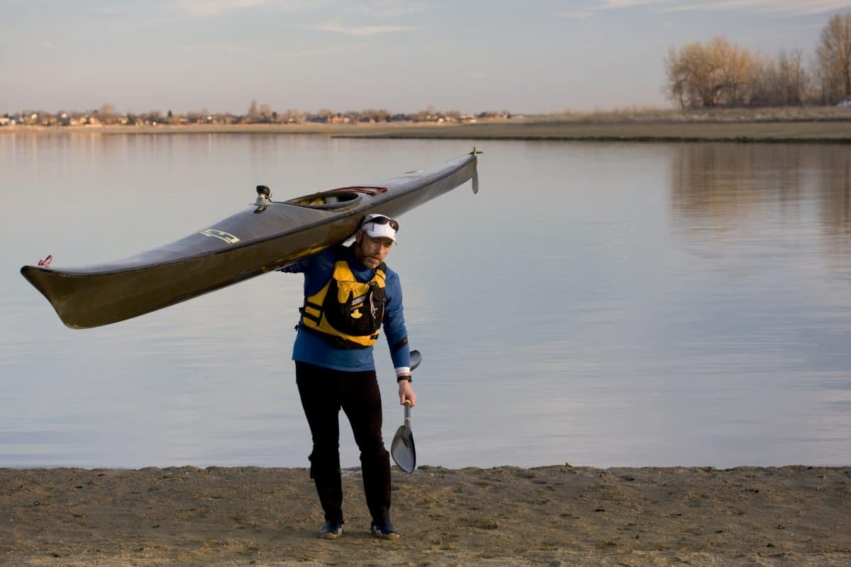 Man carrying a Kayak on shoulder
