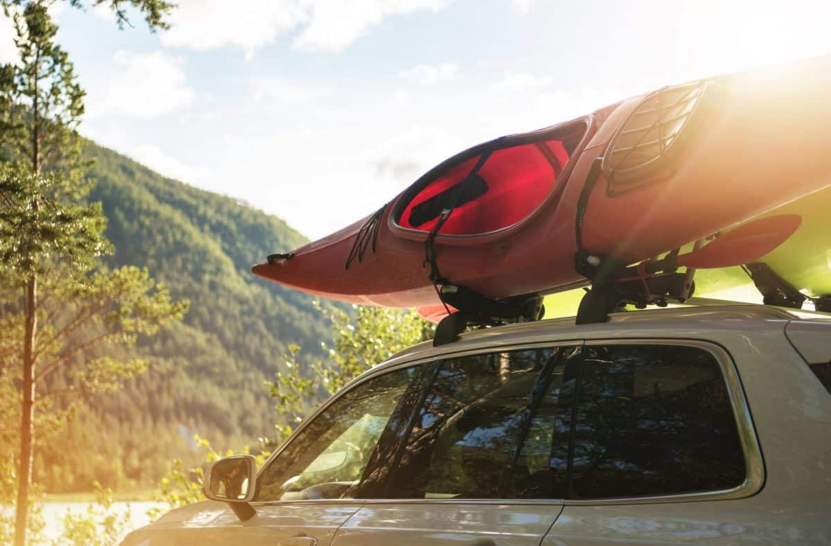 Car with red kayak on  j-cradles roof rack