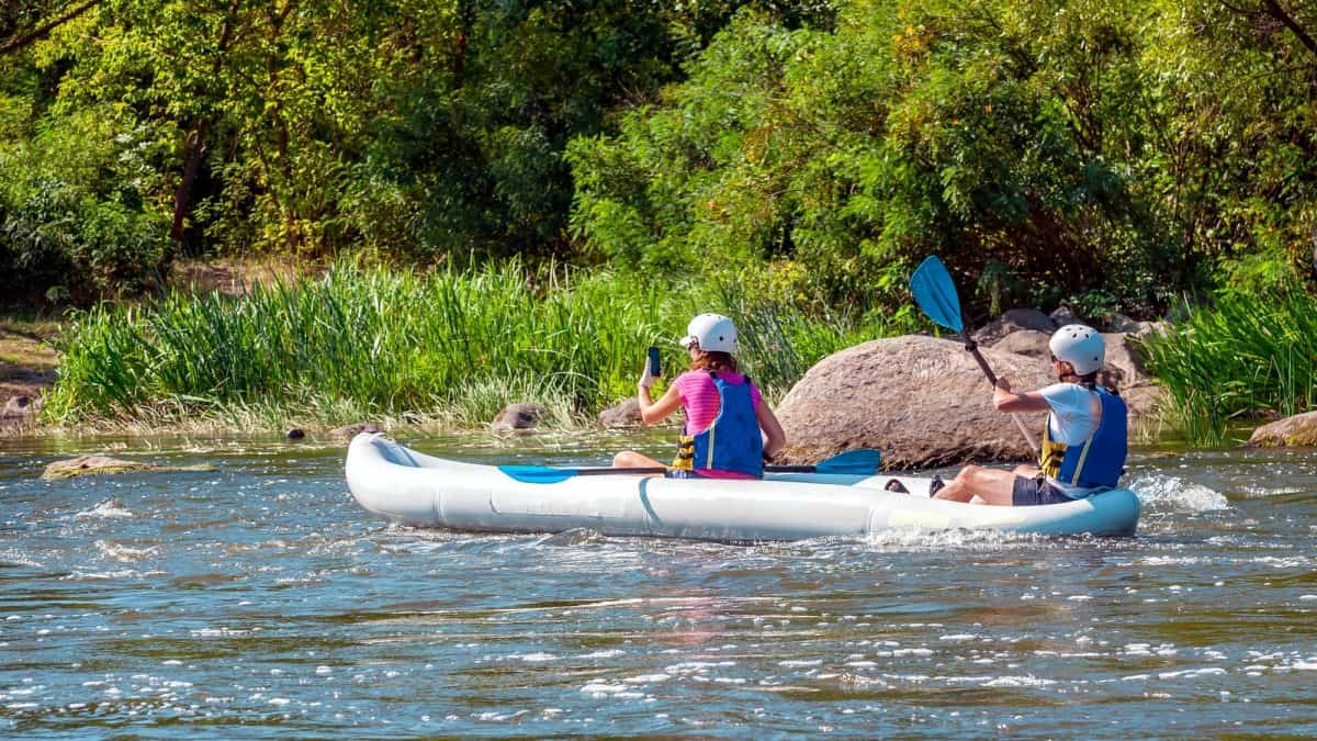 Two girls in a large inflatable kayak on the river.