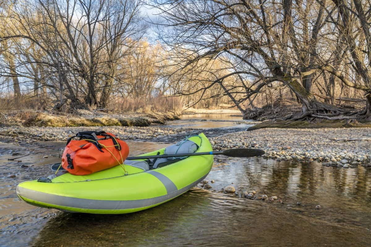 whitewater inflatable kayak with a paddle and waterproof duffel on a river  shore