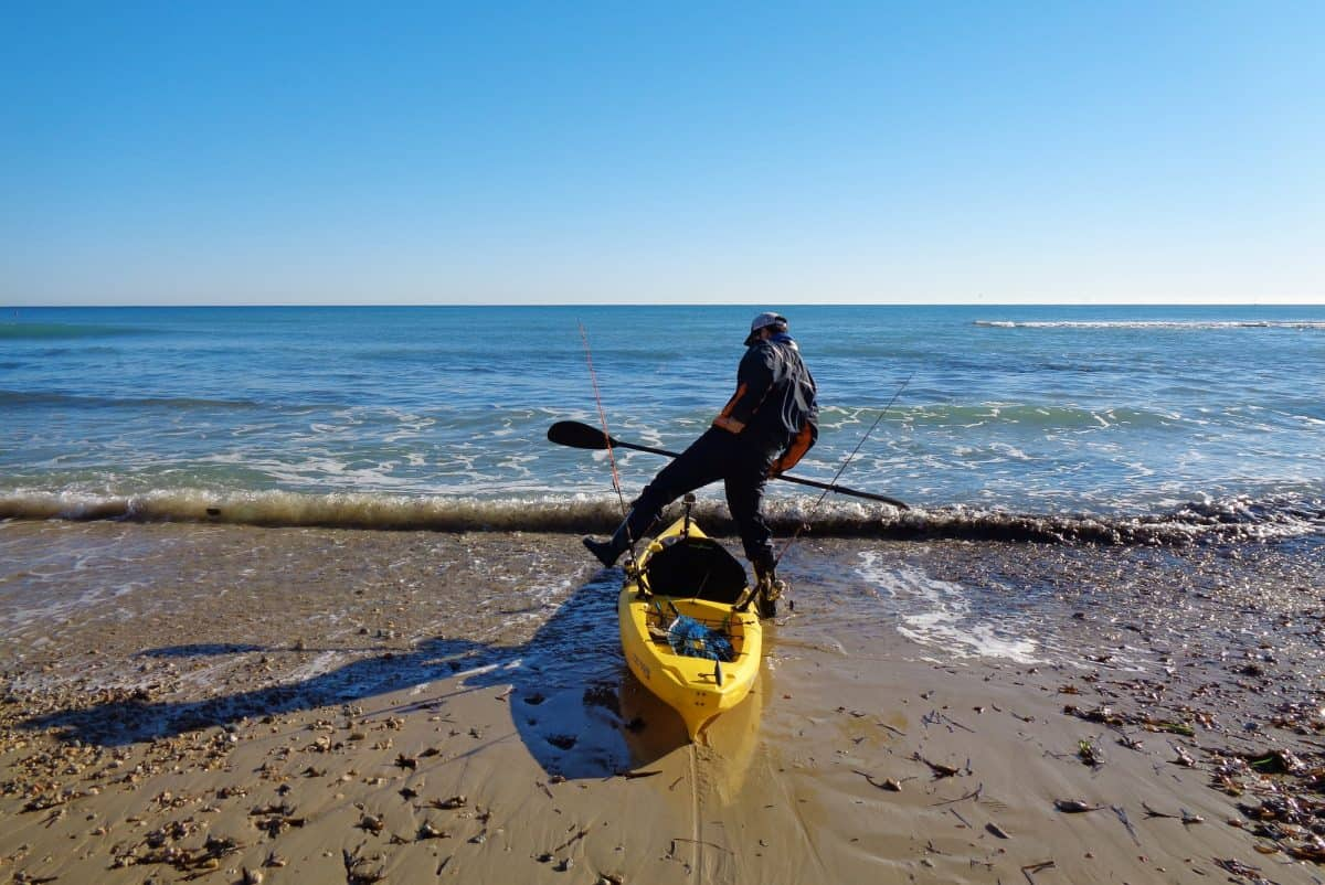 Kayak fisherman on the shore of the sea