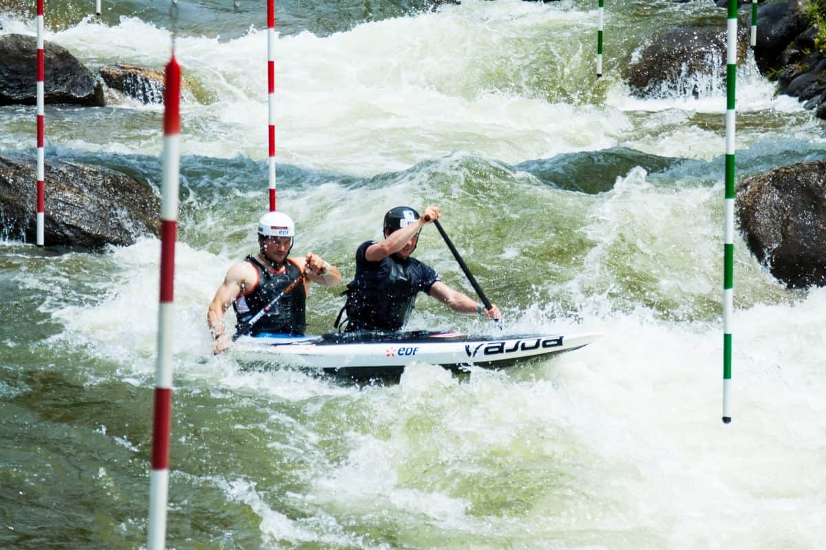 Two men in tandem kayak in rapid white water