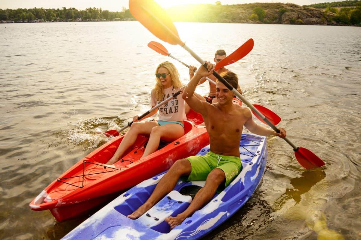 riends Having Fun on SIt-On_Top Kayaks on Beautiful River or Lake at Sunset