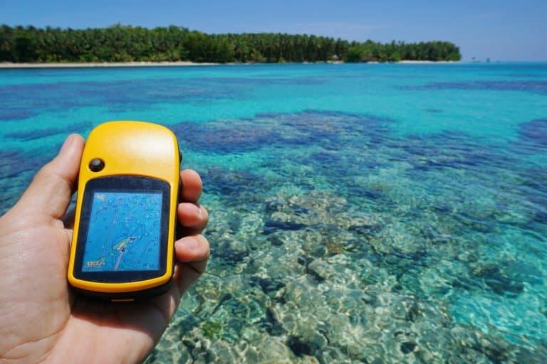 GPS satellite navigator in hand over tropical sea
