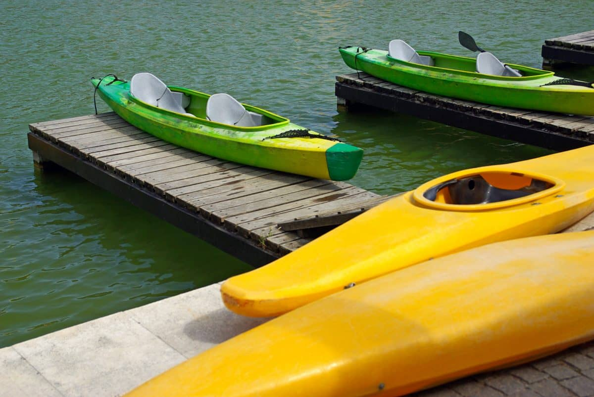 Two sit-in and two sit-on-top kayaks on a pier