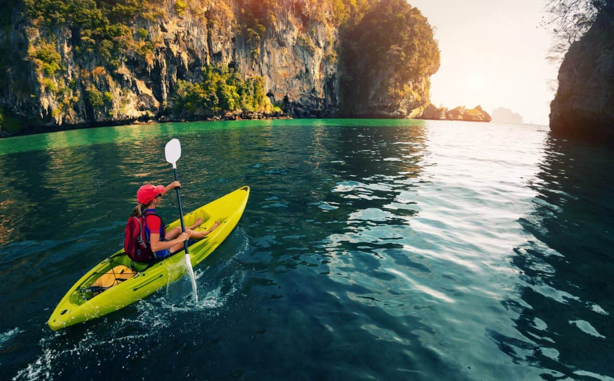 Young lady paddling the Sit-in kayak in the calm bay with limestone mountains