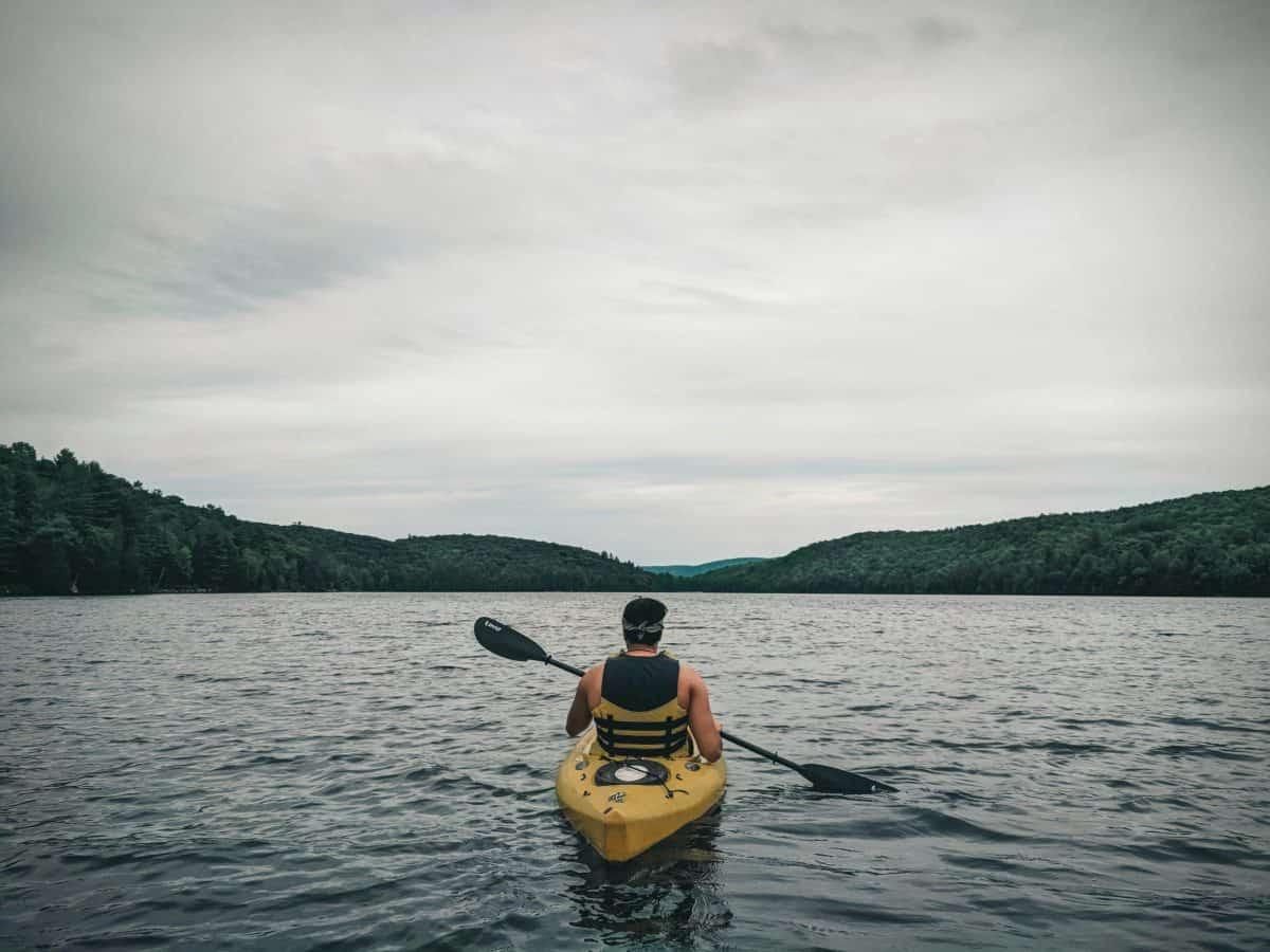 Man in Sit in kayak facing outward towards lake