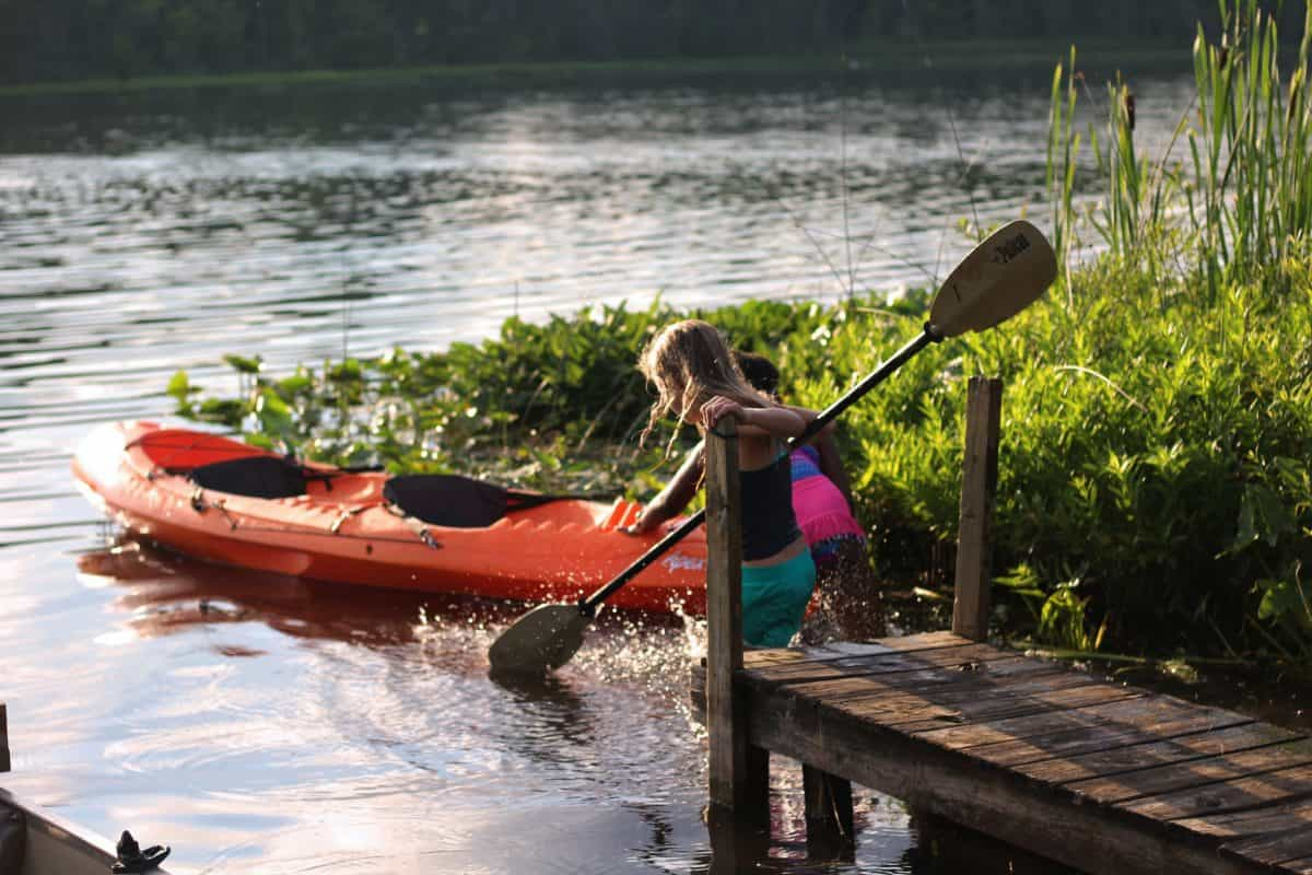 Two children wading to water towards orange kayak with black kayak seat