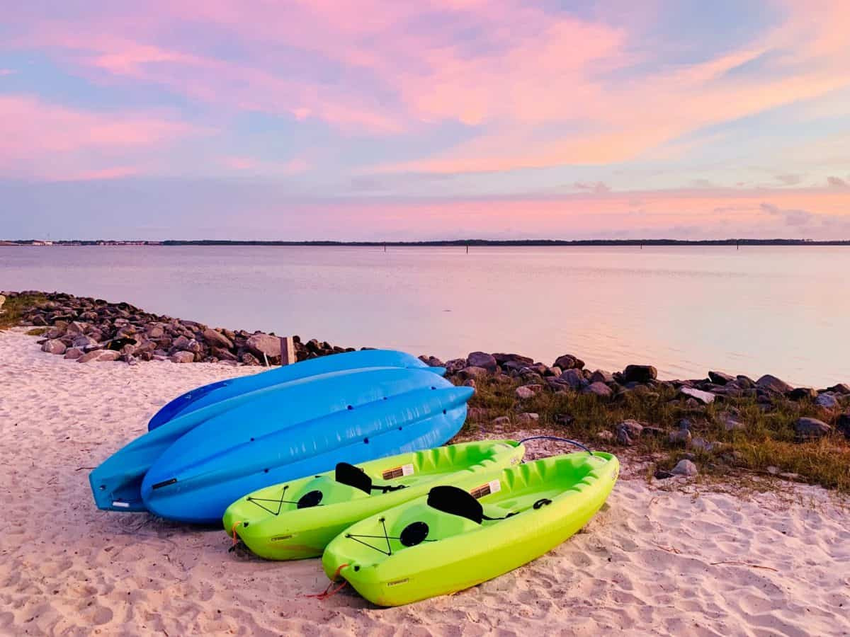 SIt on top kayaks on beach, two blue, two green, with kayak seat
