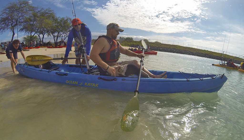 Men entering tandem fishing kayak on the shore