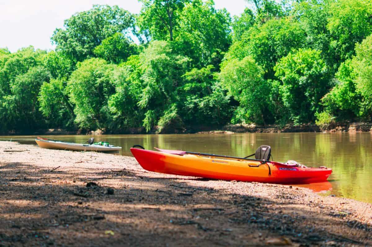 Oranage kayak on river shore with black kayak seat