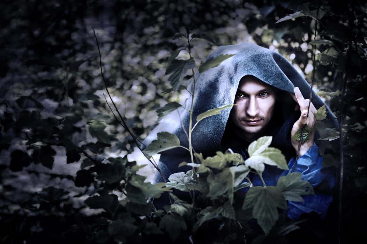 Mystery man in a raincoat with a hood hiding in the trees