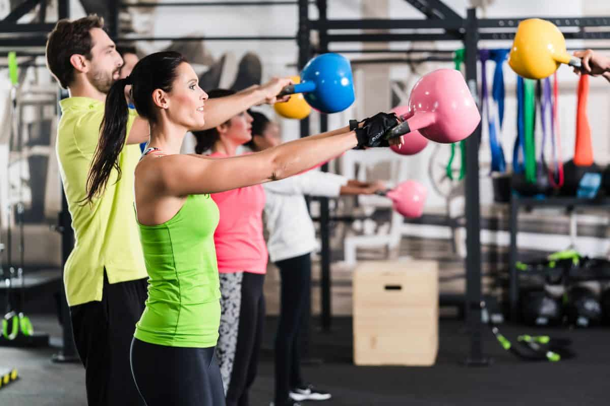 Functional fitness workout in sport gym with kettlebell swings