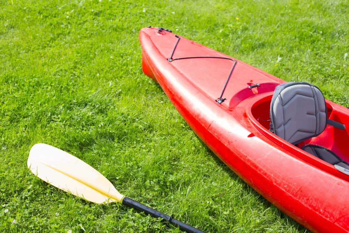 Red lightweight kayak and yellow row lays on the green grass