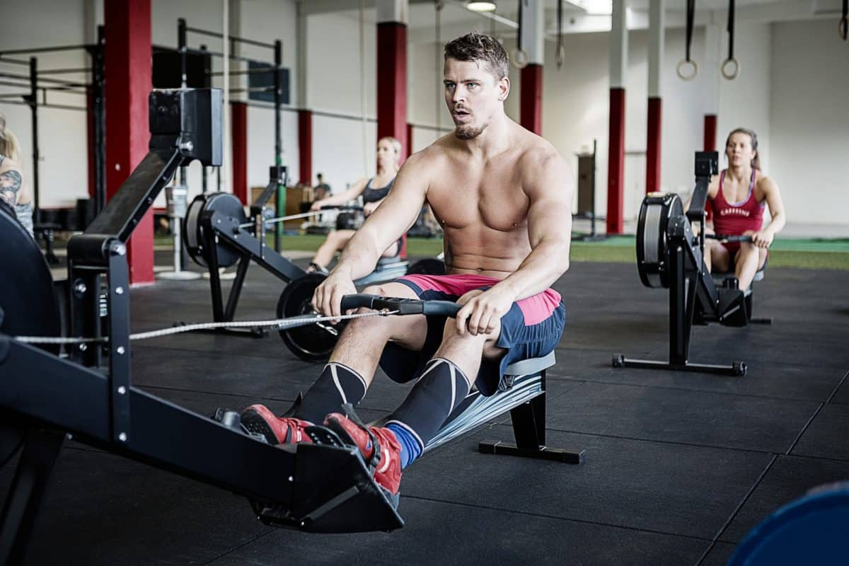 Full length of young shirtless man using rowing machine in gymnasium