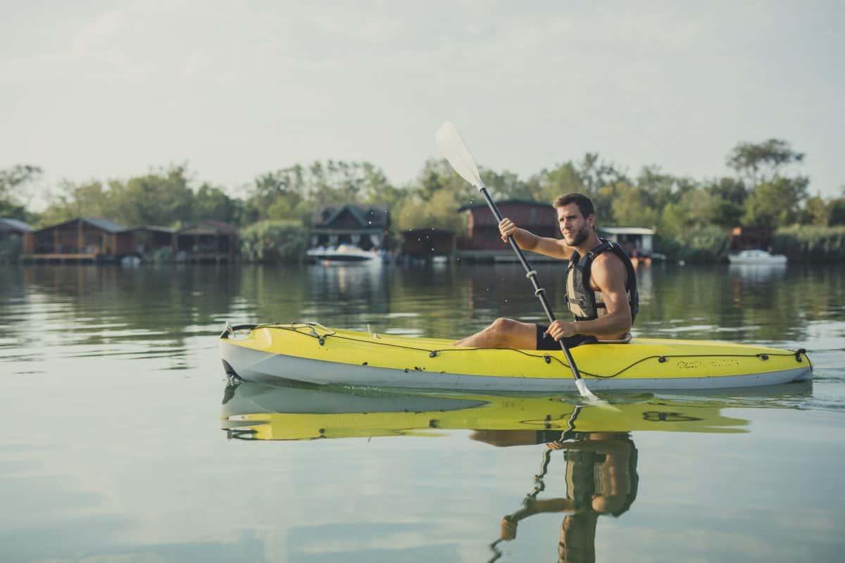 Handsome Caucasian man kayaker paddling on the river.