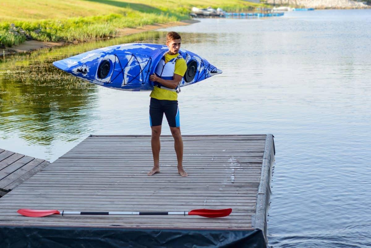 Younger man carrying kayak