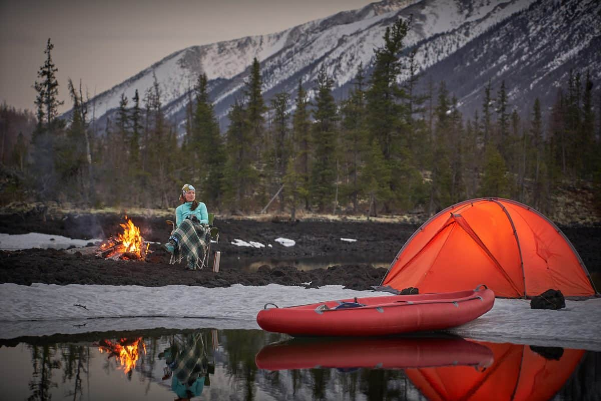 View of camp life. Woman sitting near campfire, drinking tea or coffe and have a rest. Orange tent next to lake shore. Canoe on water near the tent. Snow mountains on background.