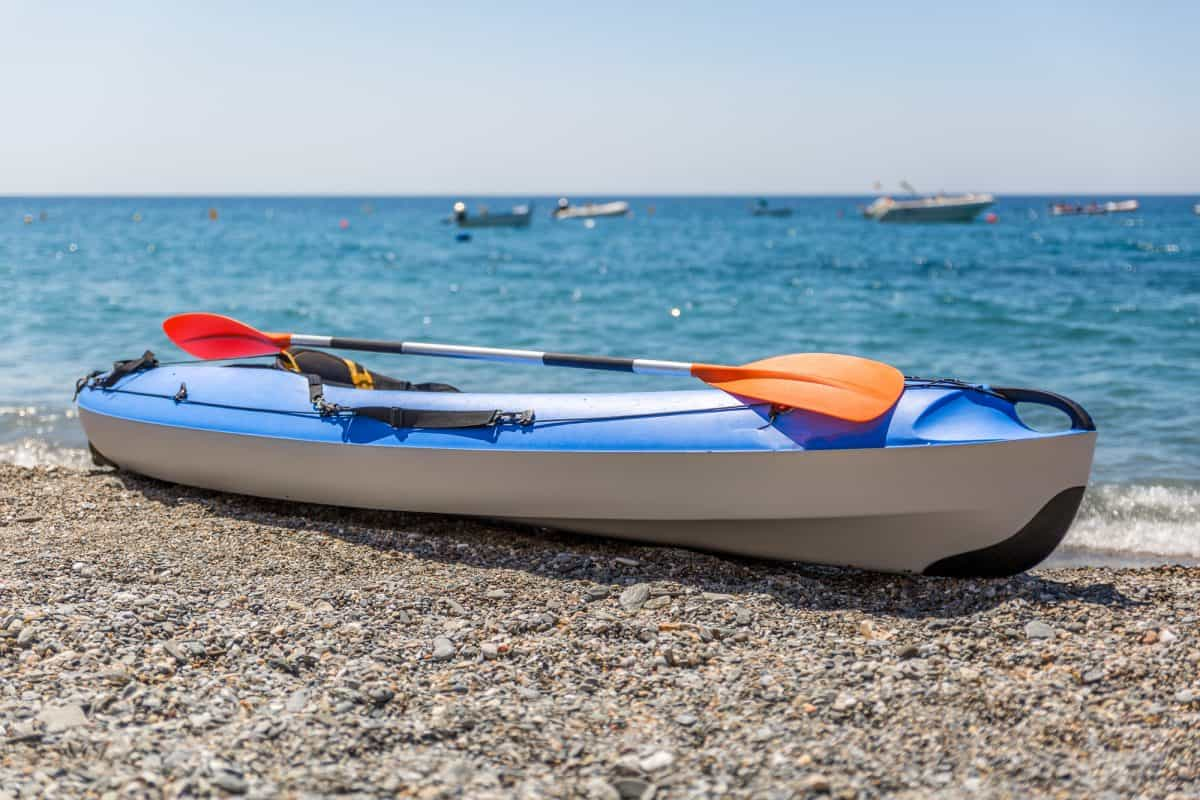 Mixed hard shell and inflatable kayak on rocky beach