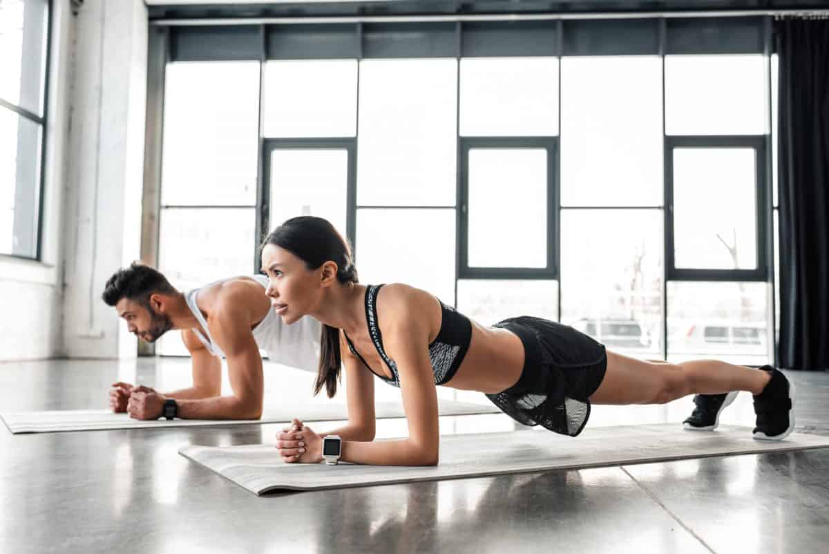 Couple in fitness gear performing plank exercise