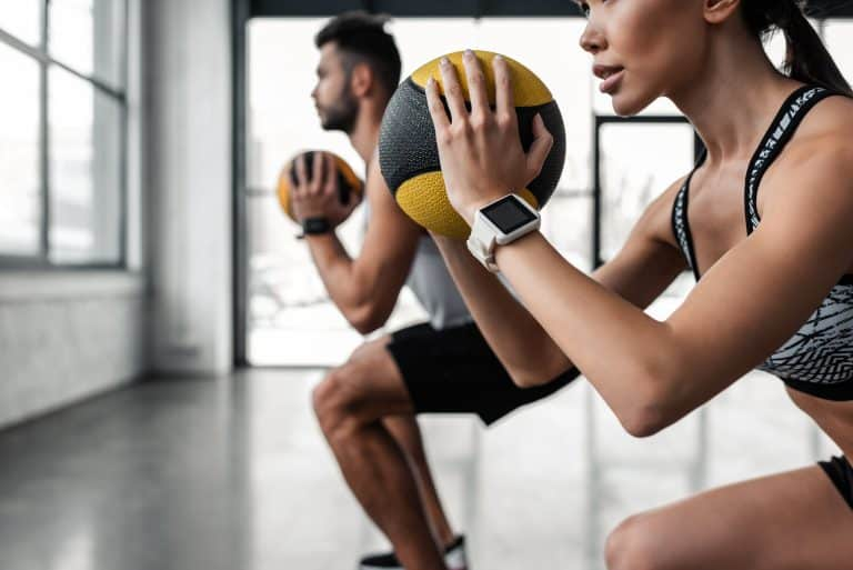 Couple training for kayaking with medicine balls