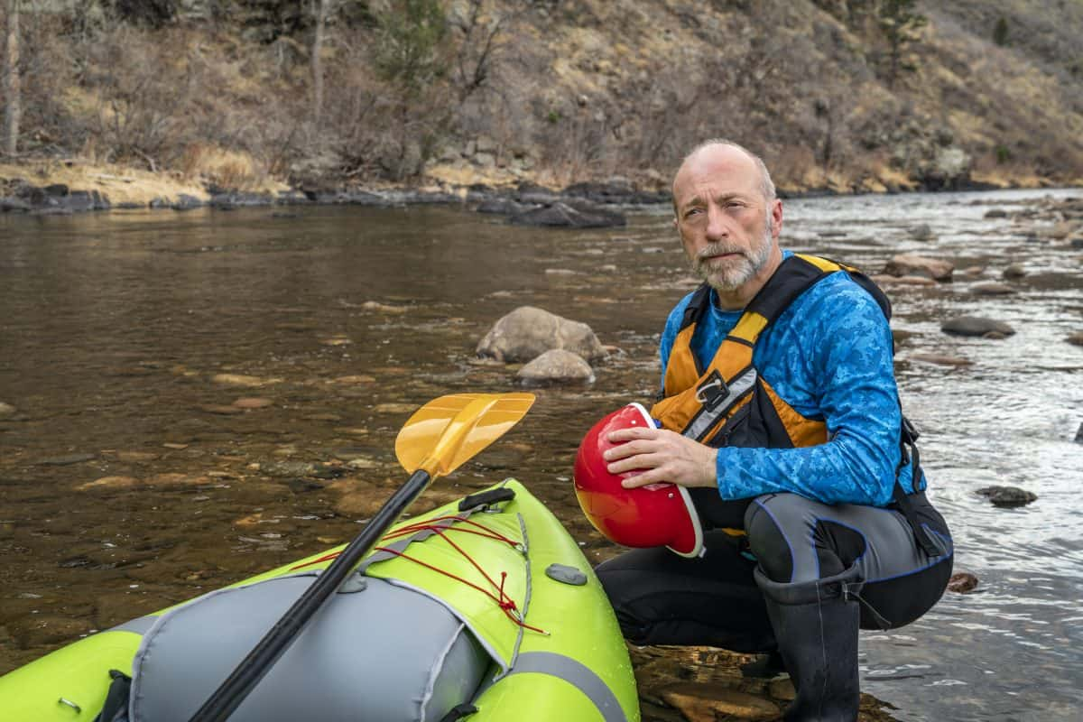 senior paddler in life jacket with a whitewater inflatable kayak -
