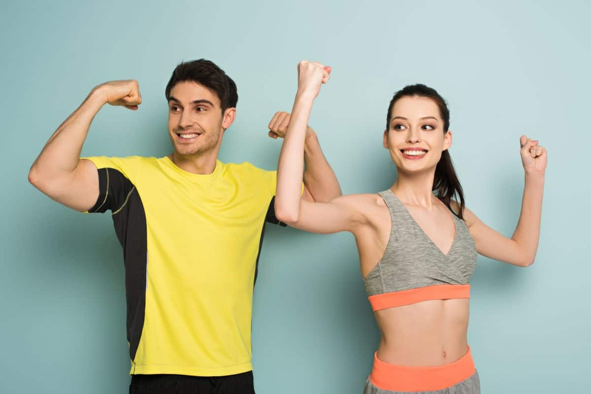 Man and woman showing muscles wearing sports tops