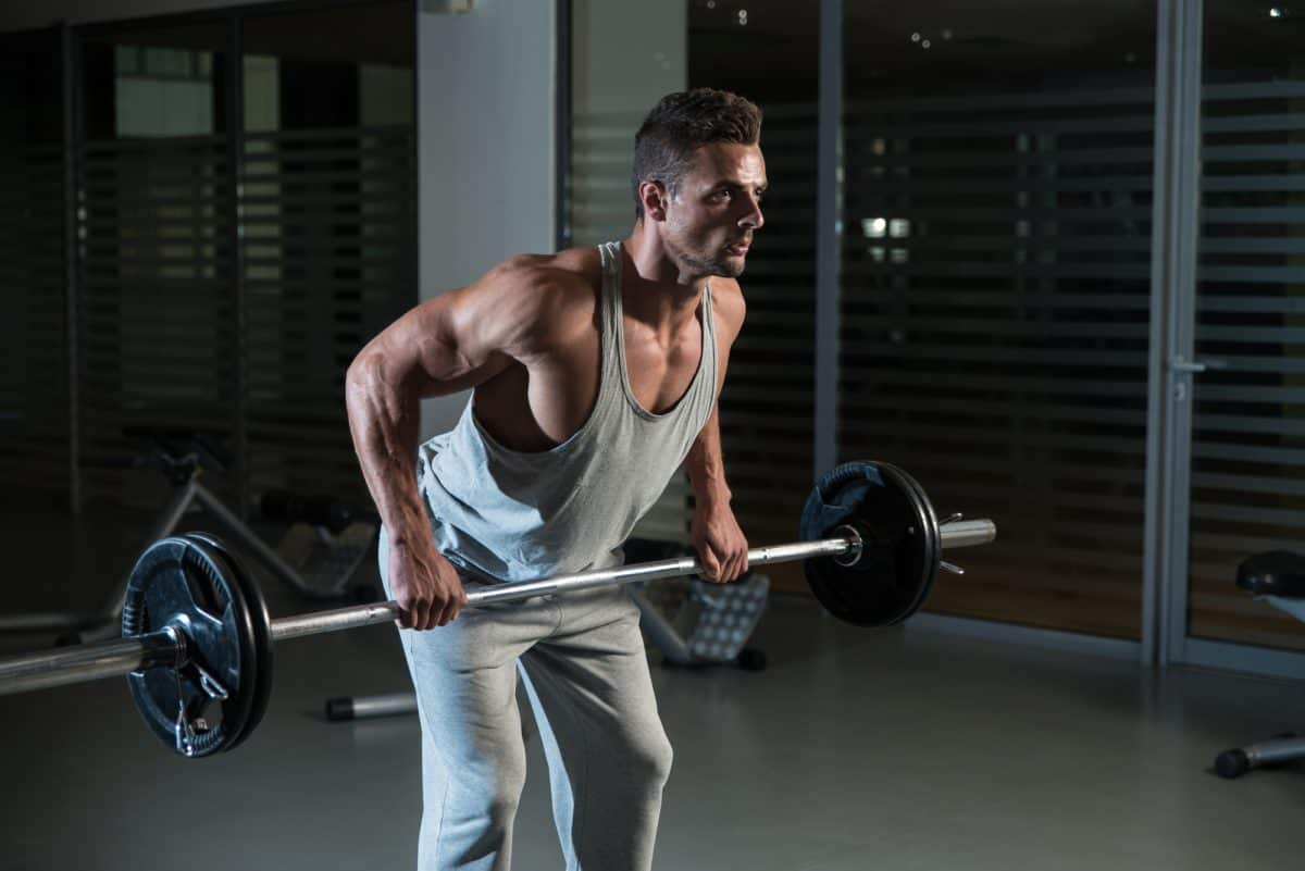 Man Doing bend over row Exercise For Back With Barbell