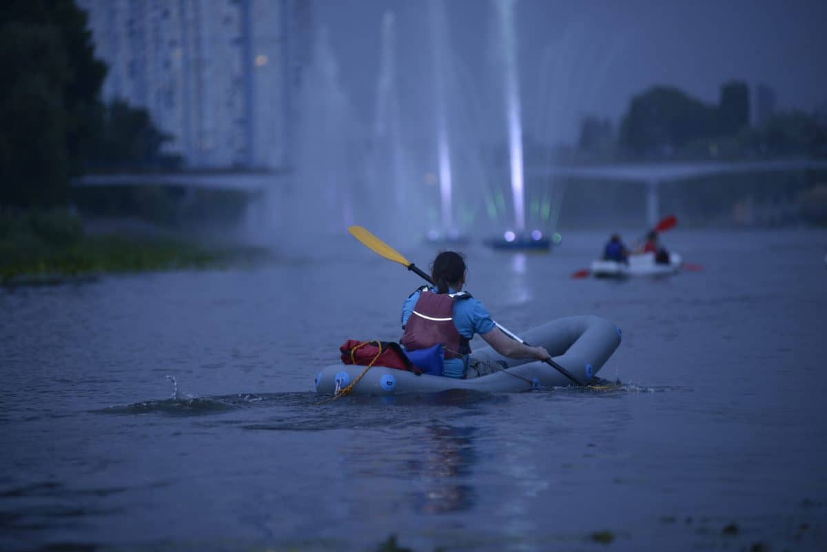 Kayak lights for kayaking at night - Man rowing kayak in the rain falling, evening light