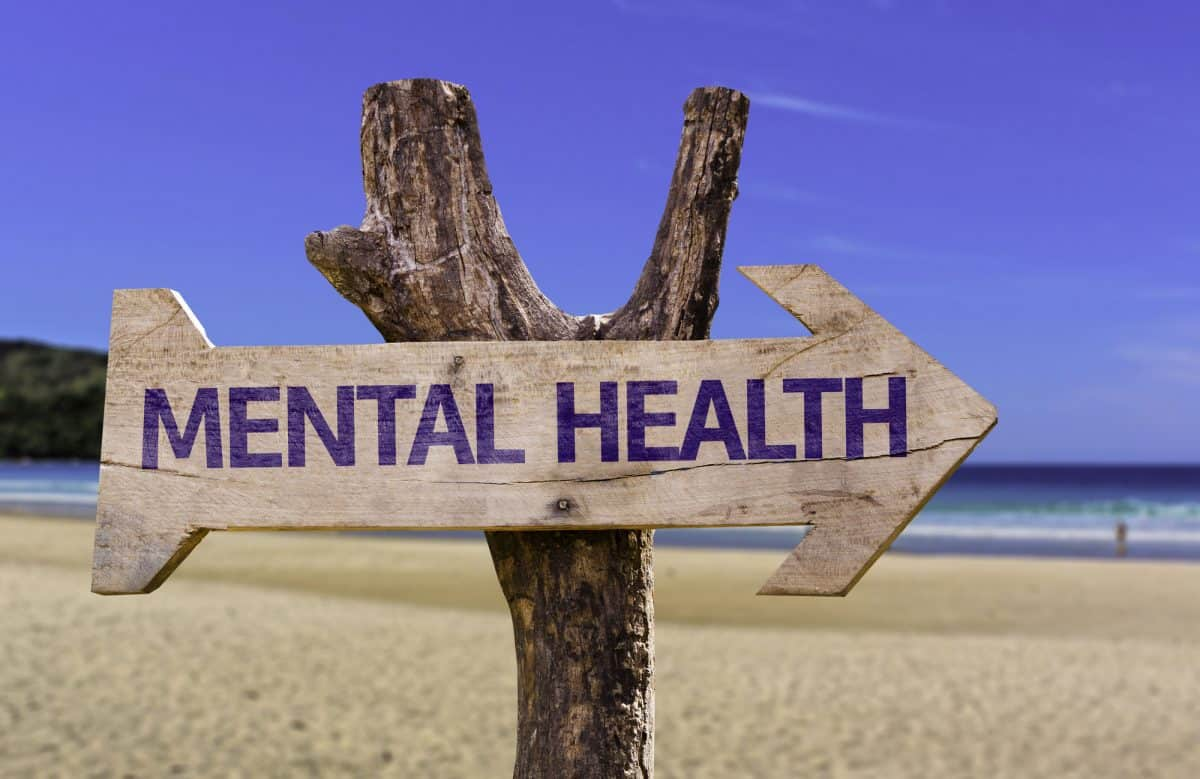 A sign saying mental health this way on beach