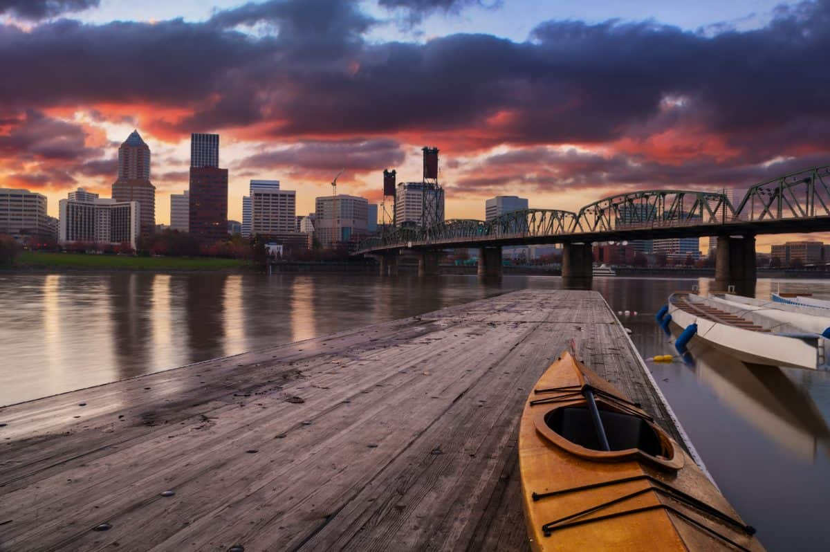 Kayaking at night. Portland, Oregon Panorama.  Sunset scene with dramatic sky and light reflections on the Willamette River.