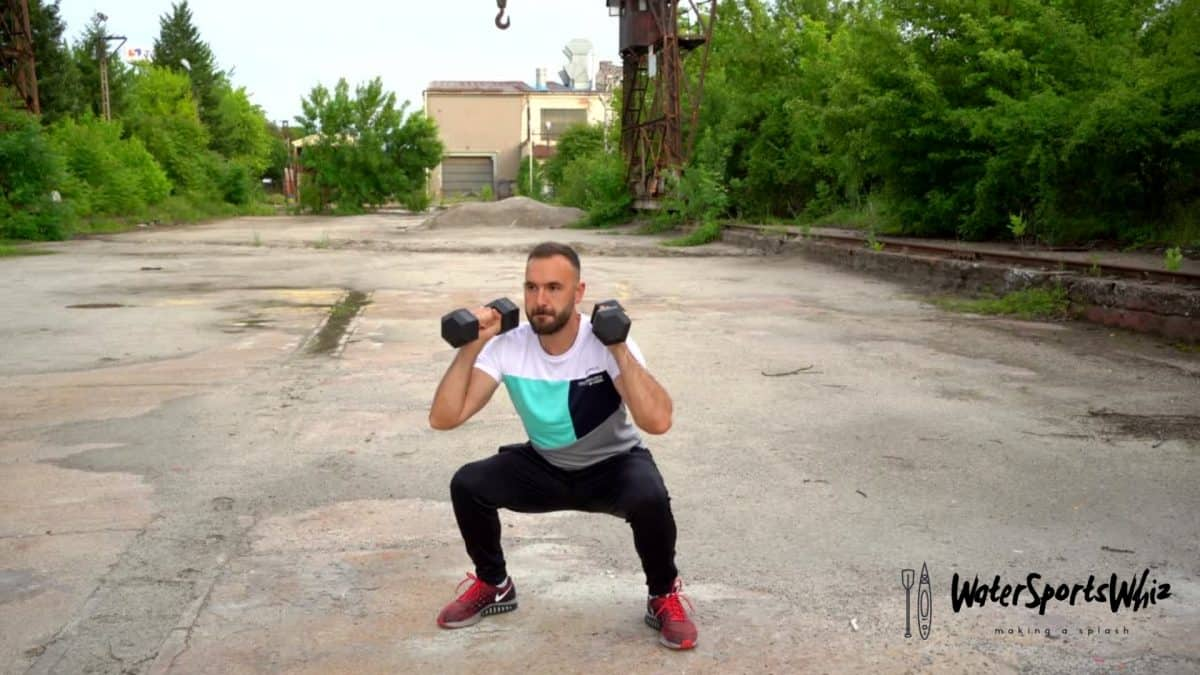 Man performing a dumbbell squat and press