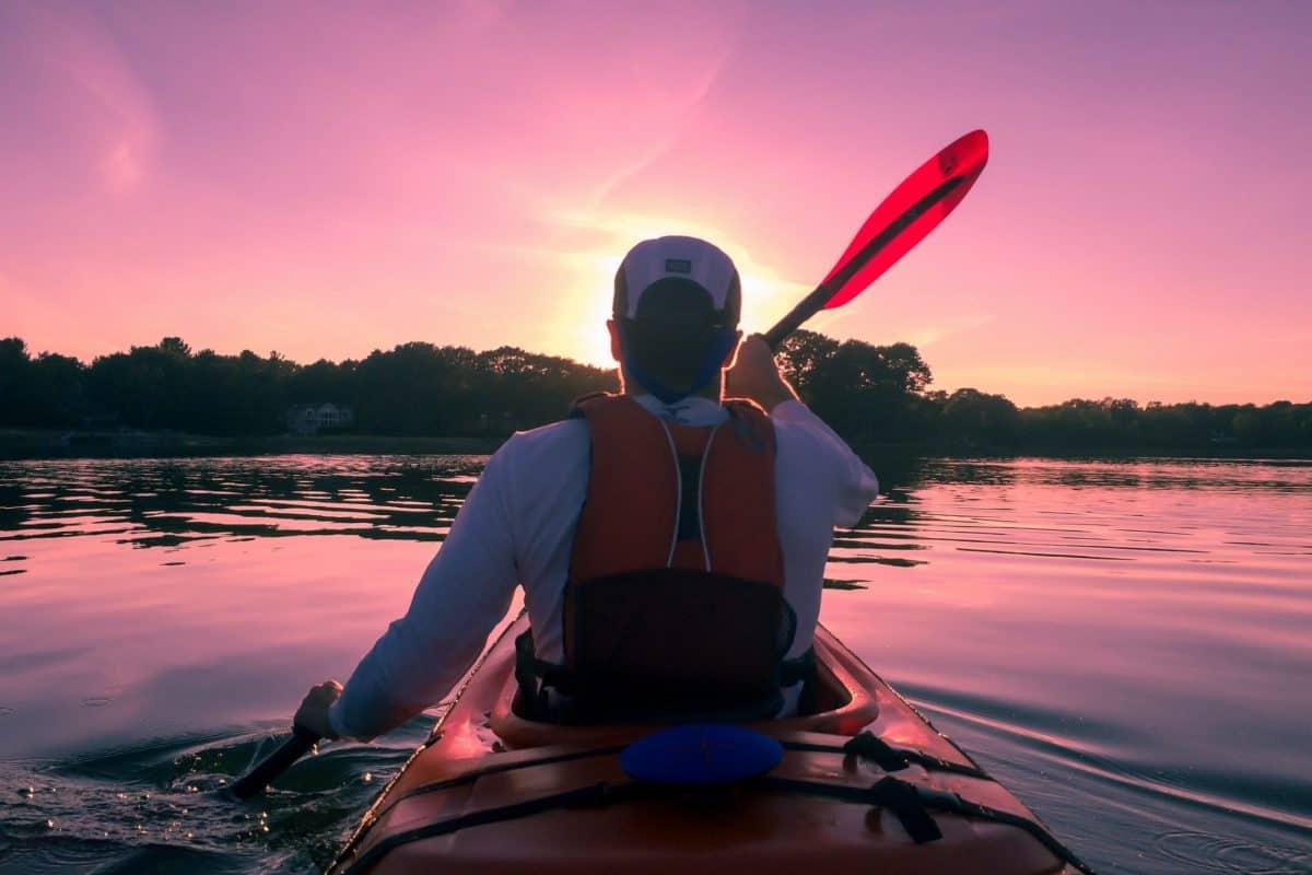 Kayaker paddling at sunset