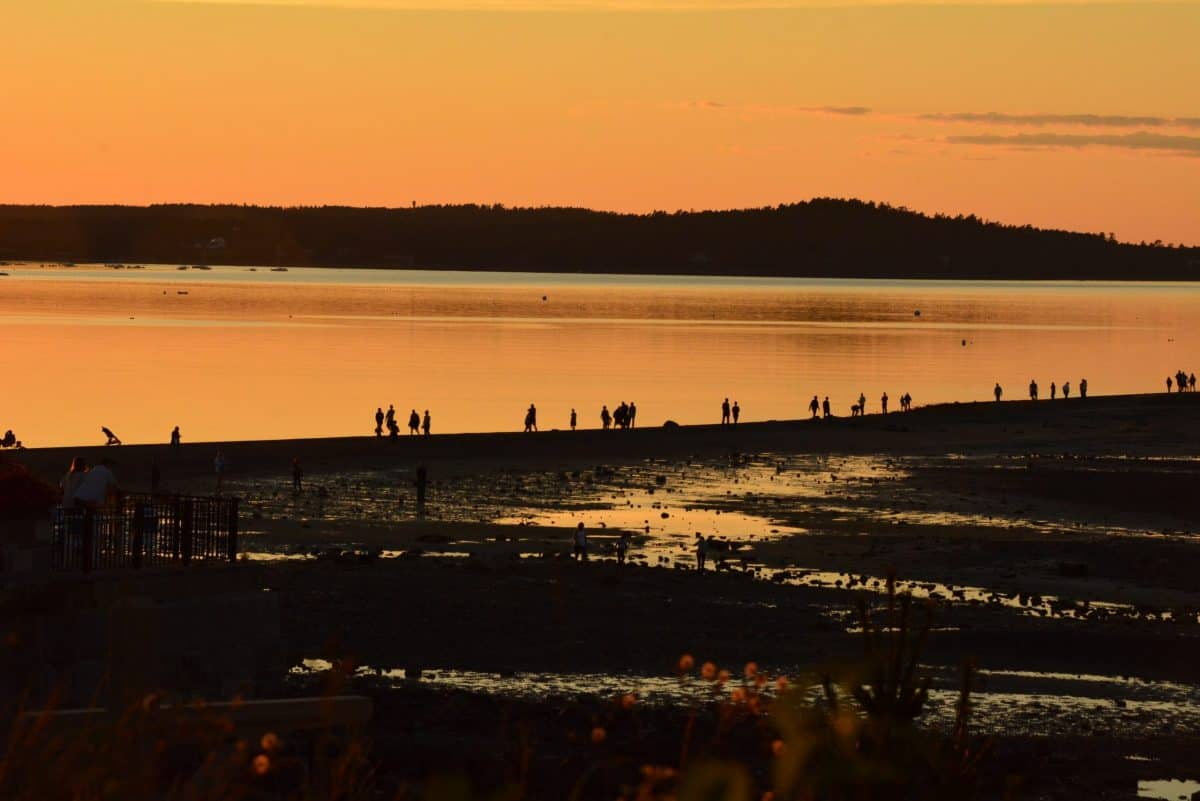 Sunset at a river with the tide out.  People walk along the shore line