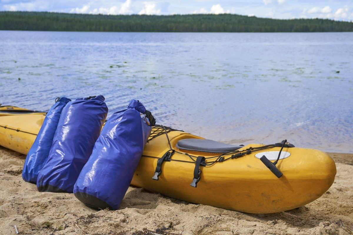 Two dry bag laying next to a yellow kayak