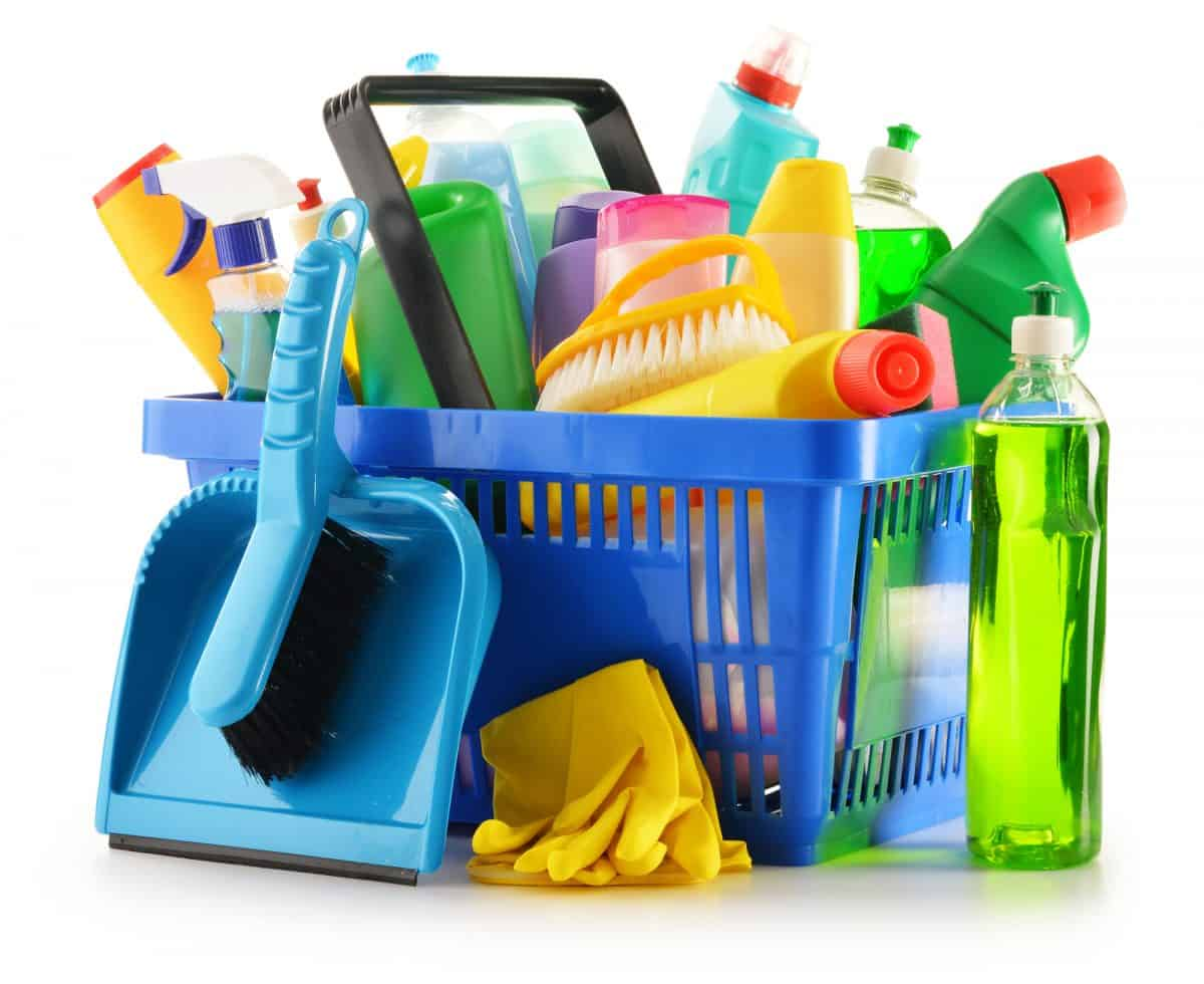 hopping basket with detergent bottles and chemical cleaning supplies isolated on white