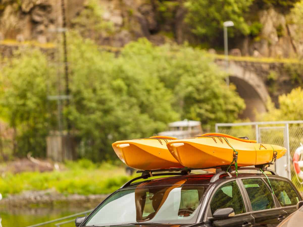 Two yellow kayaks strapped to a car roof rack