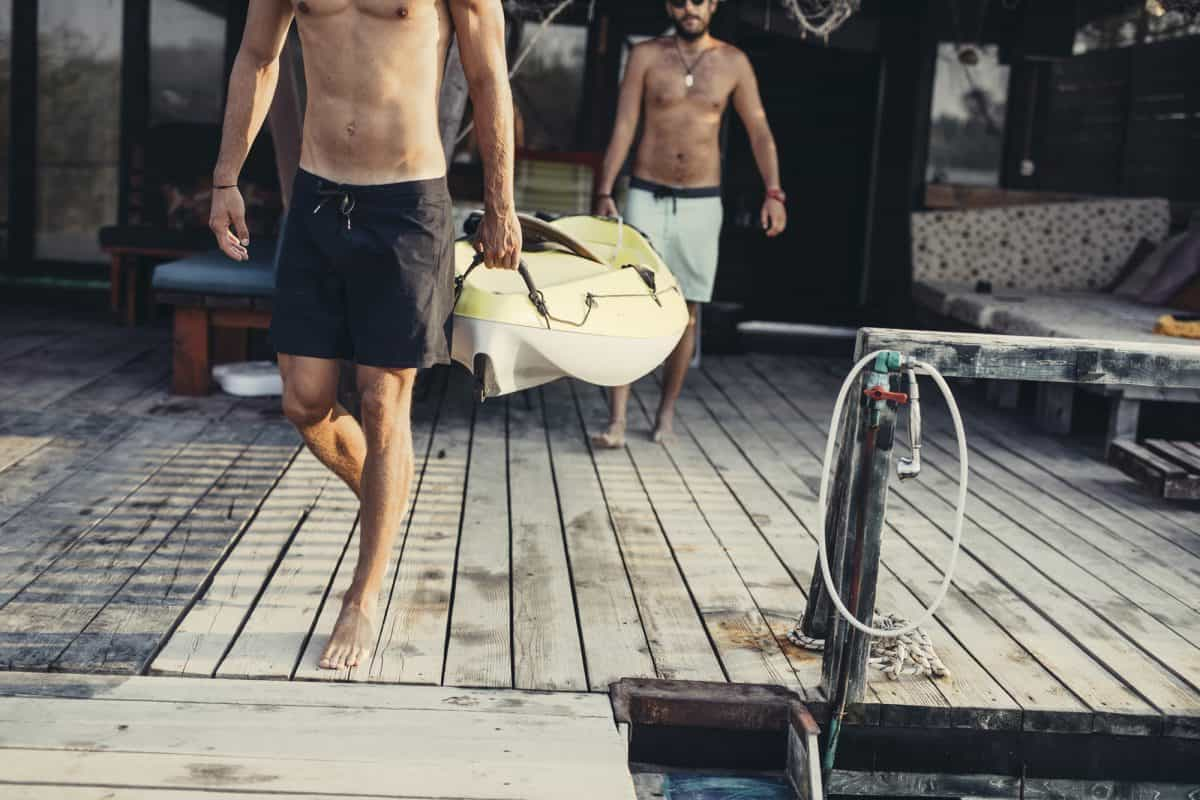 Kayak weight - how much does a kayak weigh. Men carrying a kayak on wooden deck.