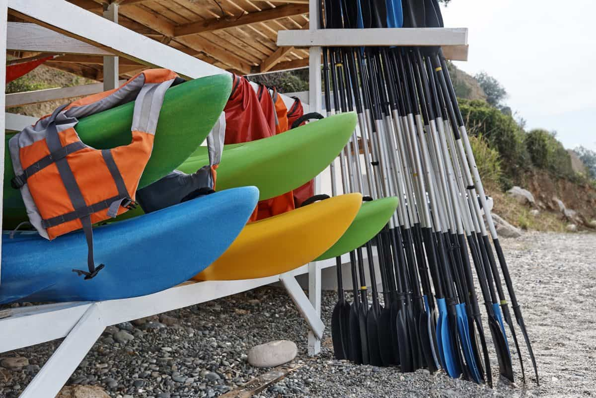 Kayaks, life jackets, oars under a wooden storage rack on the beach