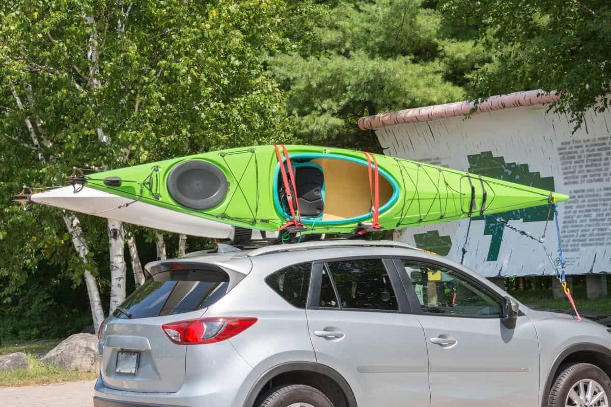 Kayak on kayak roof rack system, tired down with straps, bow and stern lines