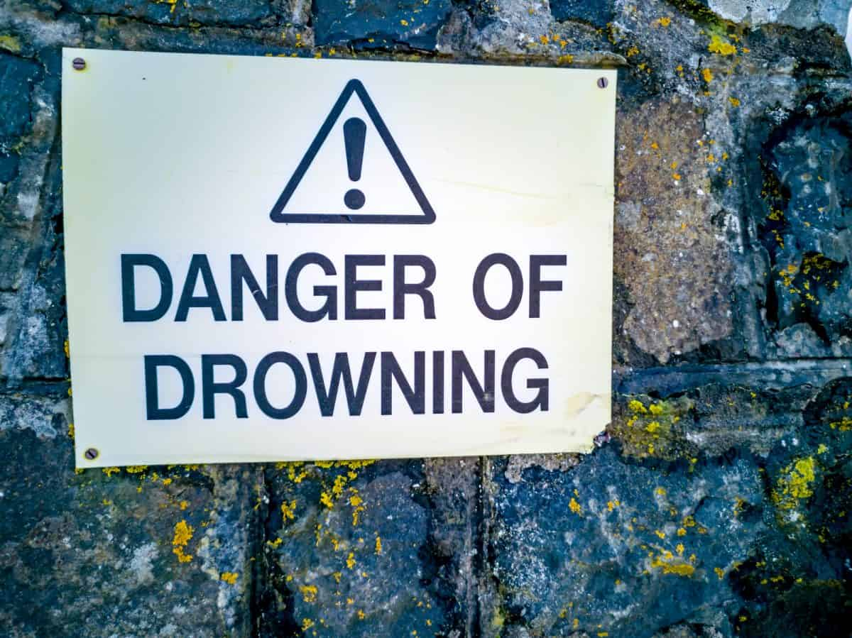 Low-Dam - Warning sign danger of drowning on a stone wall