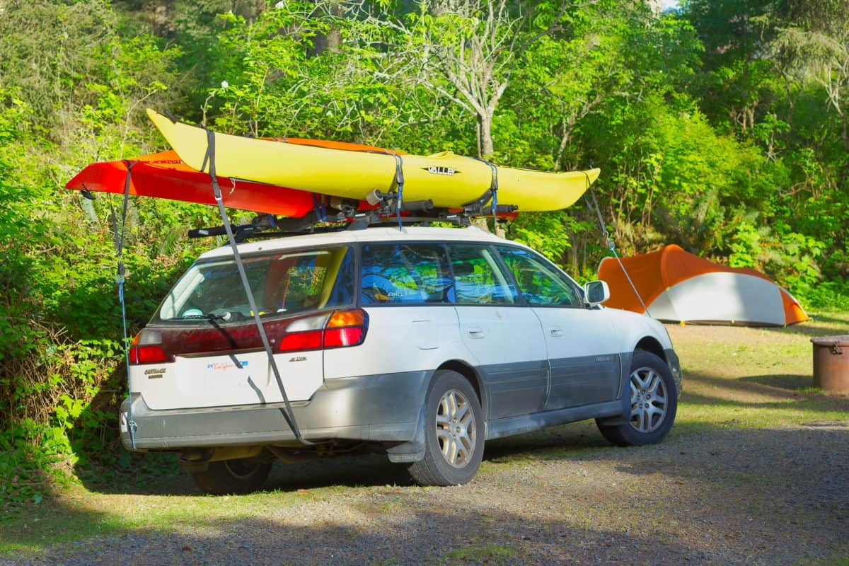 One red, one yellow kayak on the roof of a car
